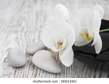 Orchids and  massage stones   on a old wooden background