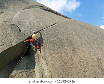 Orco Valley, Piedmont, Italy: Rock climber on cracked granite wall.