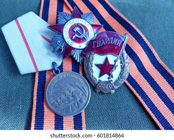 """Orden of the """"Great patriotic war"""", a sign of """"Guards"""", Medal """"For the Defense of Stalingrad"""" on St. George's ribbon. Closeup. Heirloom. Memory. May 9 - Victory Day."""