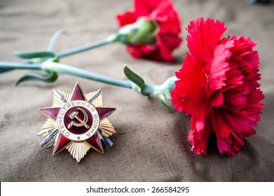 Order of the patriotic war 1st class and two red carnations. Still life dedicated to Victory Day. 9 May.