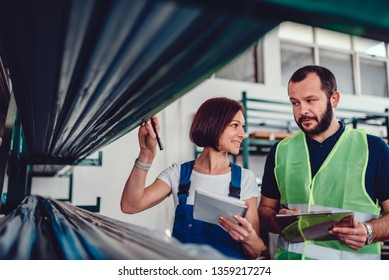 Order picker collecting products in the warehouse of industrial factory