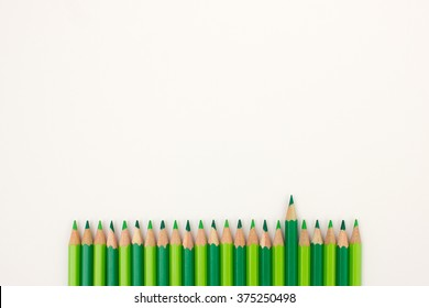 Ordered group of bright green pencils on white background with one pen standing out from the crowd - useful background image for presentations