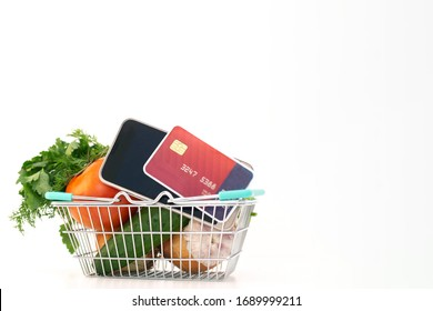 ordering food at home in connection with isolation from the coronavirus. phone and card. tomato, cucumber, greens in basket. copyspace