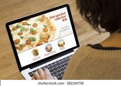 ordering food online concept: woman with a laptop showing fast food website on screen. Screen graphics are made up.