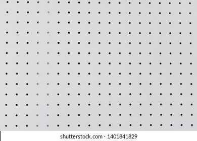 orderly holes or dot rows and columns on white pegboard wall.
