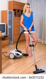 Ordinary adult  housewife in casual cleaning at home and smiling
