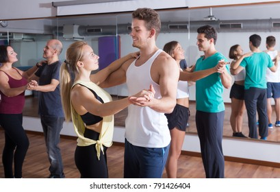 Ordinary adults dancing bachata together in dance studio