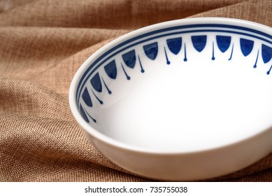 An ordinary bowl with blue prints on a brown linen cloth.
