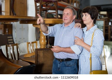 Ordinary couple is shopping the old table in the antique store