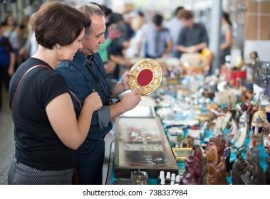 Ordinary couple of tourists study the range of flea market