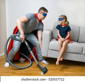 Ordinary day of superhero family. Dad doing housework.