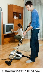 Ordinary family  cleaning with vacuum cleaner in living room