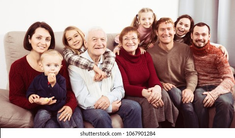 Ordinary family making numerous photos during family dinner. Focus on elderly man
