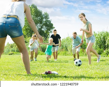 ordinary family of six people happily playing in football together outdoors on summer sunny day