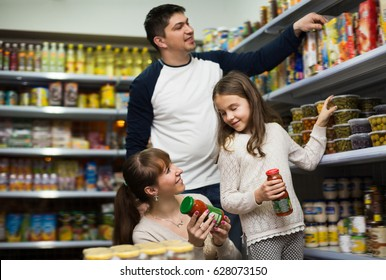 Ordinary family of three buying canned food at supermarket. Focus on woman and girl