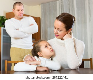 Ordinary family of three with little daughter and angry man having conflict. Focus on woman
