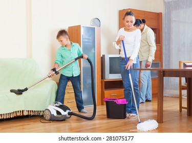 Ordinary family of three with teenager doing housework together in home