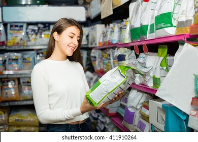Ordinary female customer buying dry food for dogs in pet shop