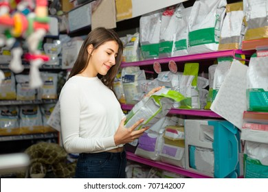 Ordinary female customer buying dry food for pets in petshop