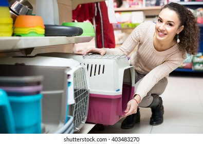 Ordinary female customer buying kennel for pet in shop