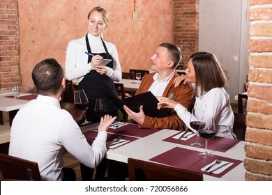 Ordinary female waiter writing down order from visitors in country restaurant