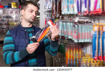 Ordinary fisherman choosing fishing lures for fishing in the sports shop