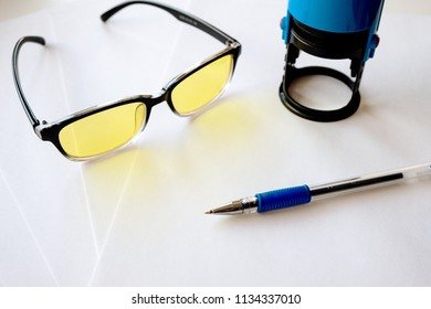 ordinary gel ballpoint pen with a rubber holder on white paper, yellow computer glasses