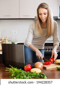 Ordinary girl  cooking with notebook in home kitchen