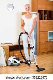 Ordinary girl hoovering surfaces at home and smiling