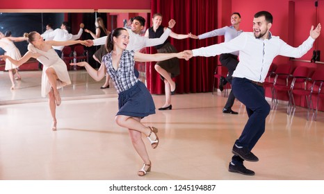 Ordinary group people dancing lindy hop in pairs in dance hall