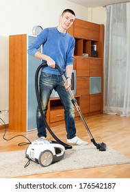 Ordinary guy with vacuum cleaner on parquet floor in home