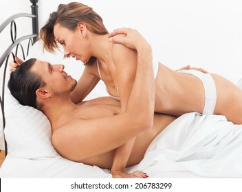 Ordinary lovers kissing and playing in bed at home