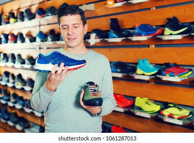 Ordinary man chooses shoes in a sports shop
