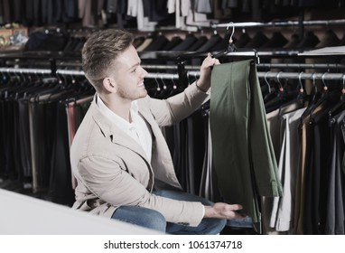 Ordinary man choosing new trousers in men's cloths store