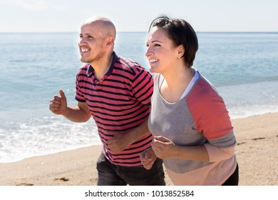 ordinary man and middle-aged woman running on the beach