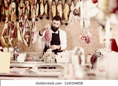 Ordinary man seller showing different sausages in butcher's shop
