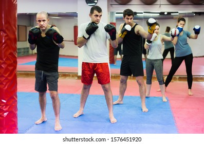 Ordinary men and women practicing boxing punches in the boxing hall