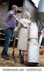 ordinary pair of farmers with milk cans