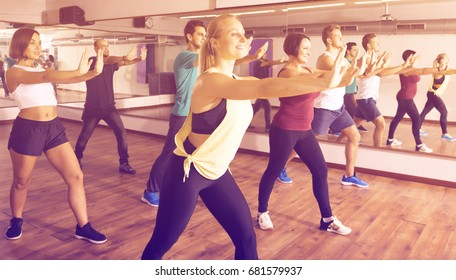 Ordinary positive people learning zumba steps in dance hall