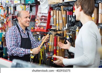 Ordinary smiling customer and  seller choosing hammer in household store