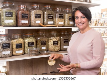 ordinary woman buyer selects herbs in store of ecological products