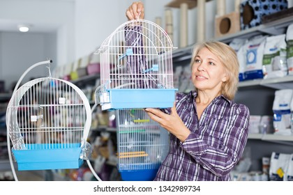 ordinary woman buying cage for bird in shop