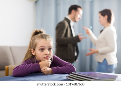 Ordinary woman and man arguing with each other while their daughter at home