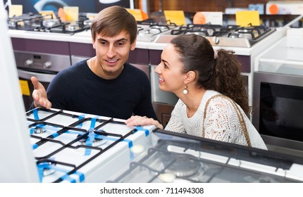 Ordinary young couple choosing gas hobs in hypermarket and smiling