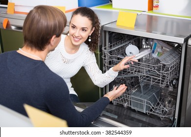 Ordinary young couple choosing new dish washing machine in appliance store