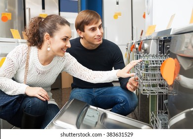 Ordinary young customers choosing new dish washing machine in supermarket