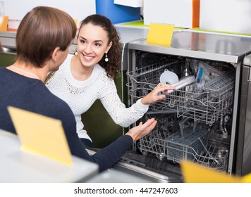 Ordinary young customers choosing new dish washing machine in appliance store