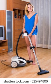 Ordinary young european housewife in casual hoovering at home and smiling