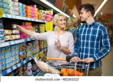 Ordinary young family choosing dairy products and smiling in hypermarket