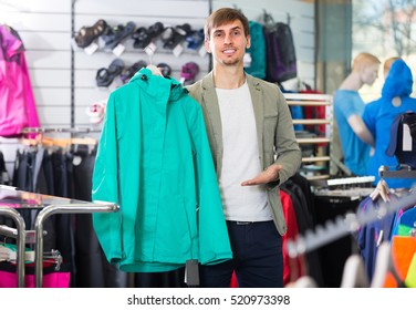 Ordinary young man picking a cardigan in the sport shop and smiling